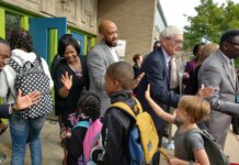 local officials high fiving kids on the first day of school