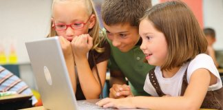 children at school looking at a computer