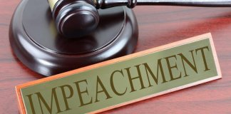 "Gavel with ""impeachment"" sign on desk"