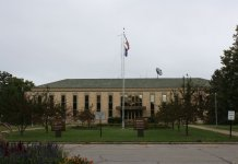 front of main building with flag atWinnebago Mental Health Institute (photo: Wikimedia Commons)