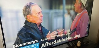 Picture of a Bloomberg ad on a television of him posing with a worker in a hardhat