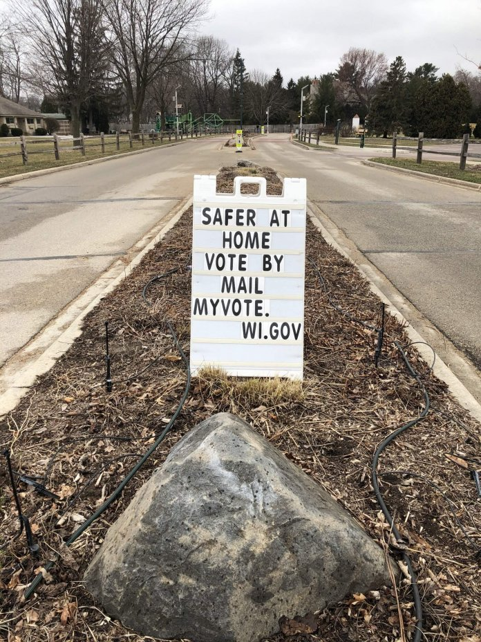 A sign urging people to vote by mail in Maple Bluff, a few blocks from the governors mansion (photo by Ruth Conniff).