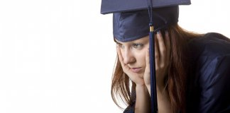 young woman in cap and gown with her hands on her head looking sad or worried