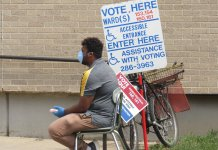A poll worker sits outside of Washington High School wearing a protective mask. (Photo by Isiah Holmes)