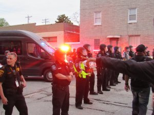 Protesters confronting riot-clad officers on the first day. Officers were blocking side streets. (Photo by Isiah Holmes)