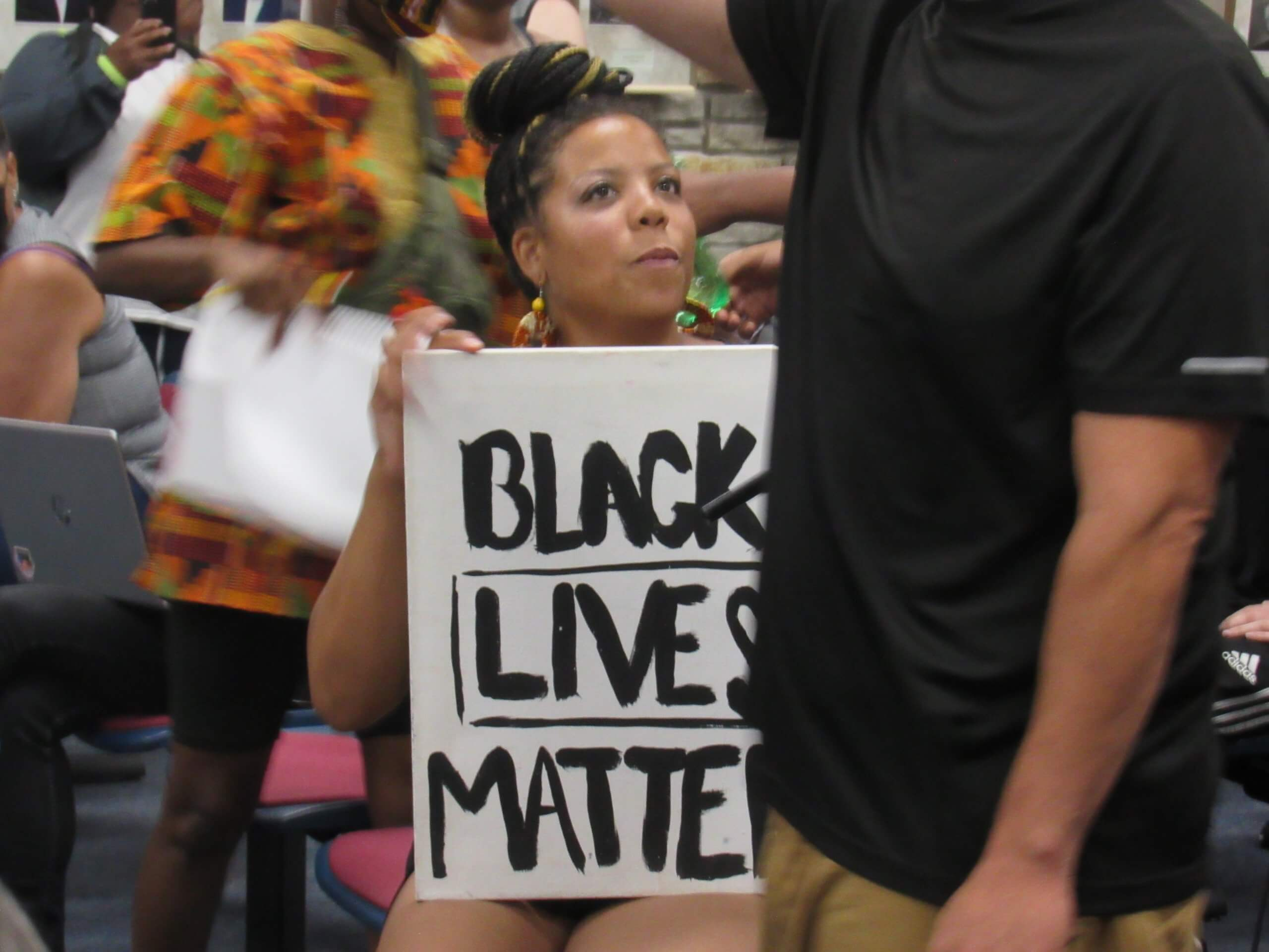 A Black Lives Matter protester attending a Wauwatosa City Council meeting. Protestes had been marching to get officer Joseph Mensah fired for killing three people over just five years. (Photo by Isiah Holmes)