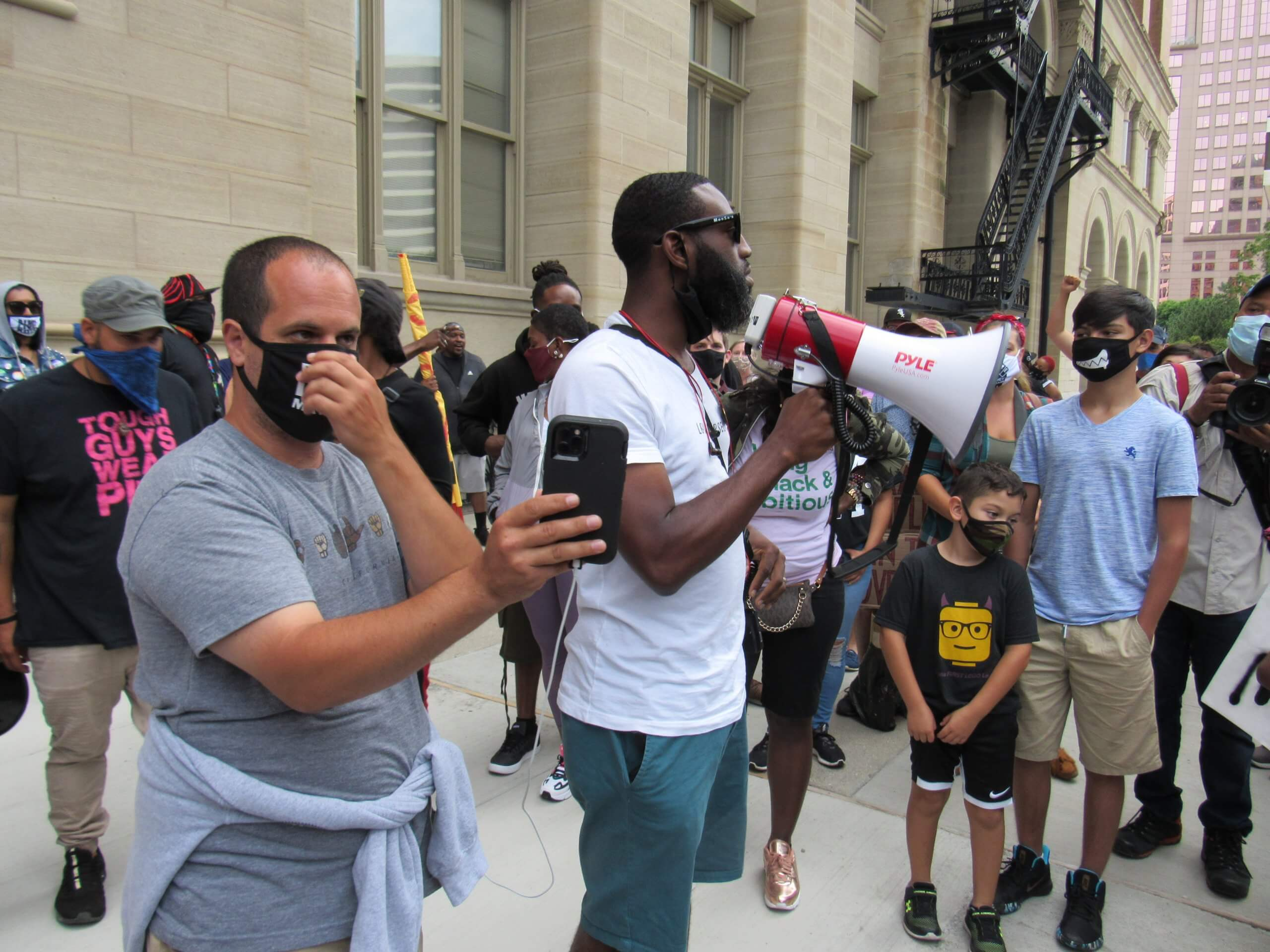 Rep. David Bowen stands beside Rep. Jonathan Brostoff as he speaks to the crowd of protesters. (Photo by Isiah Holmes)