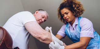 Caregiving nurse putting a bandage on a senior mans arm in his home. (Photo courtesy of Henry Ford College.)