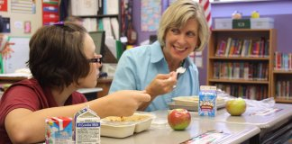 Adult (teacher or parent) eating school lunch with girl on trays in a classroom