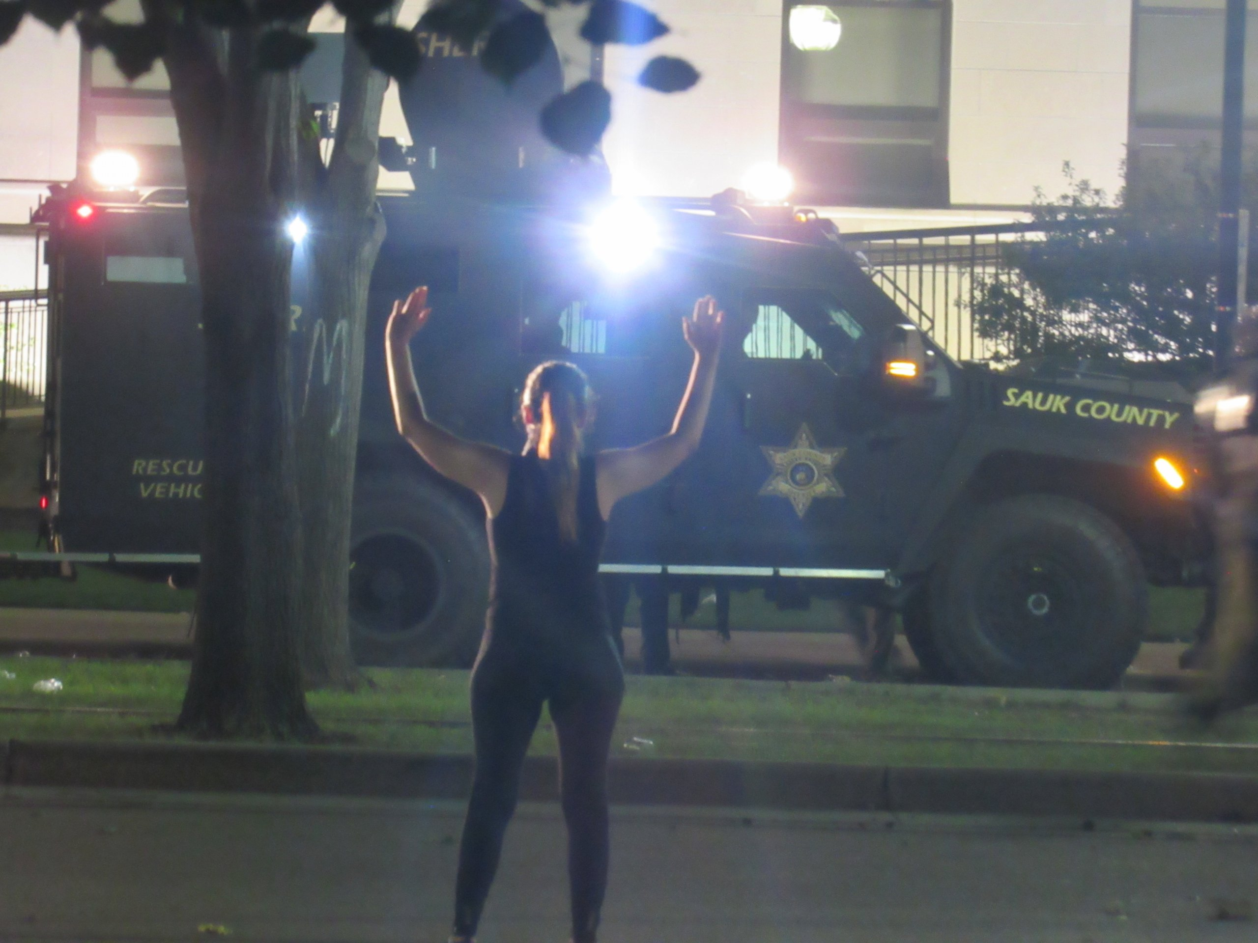 A protester stands with her hands raised in front of the armored vehicles and police. (Photo by Isiah Holmes)