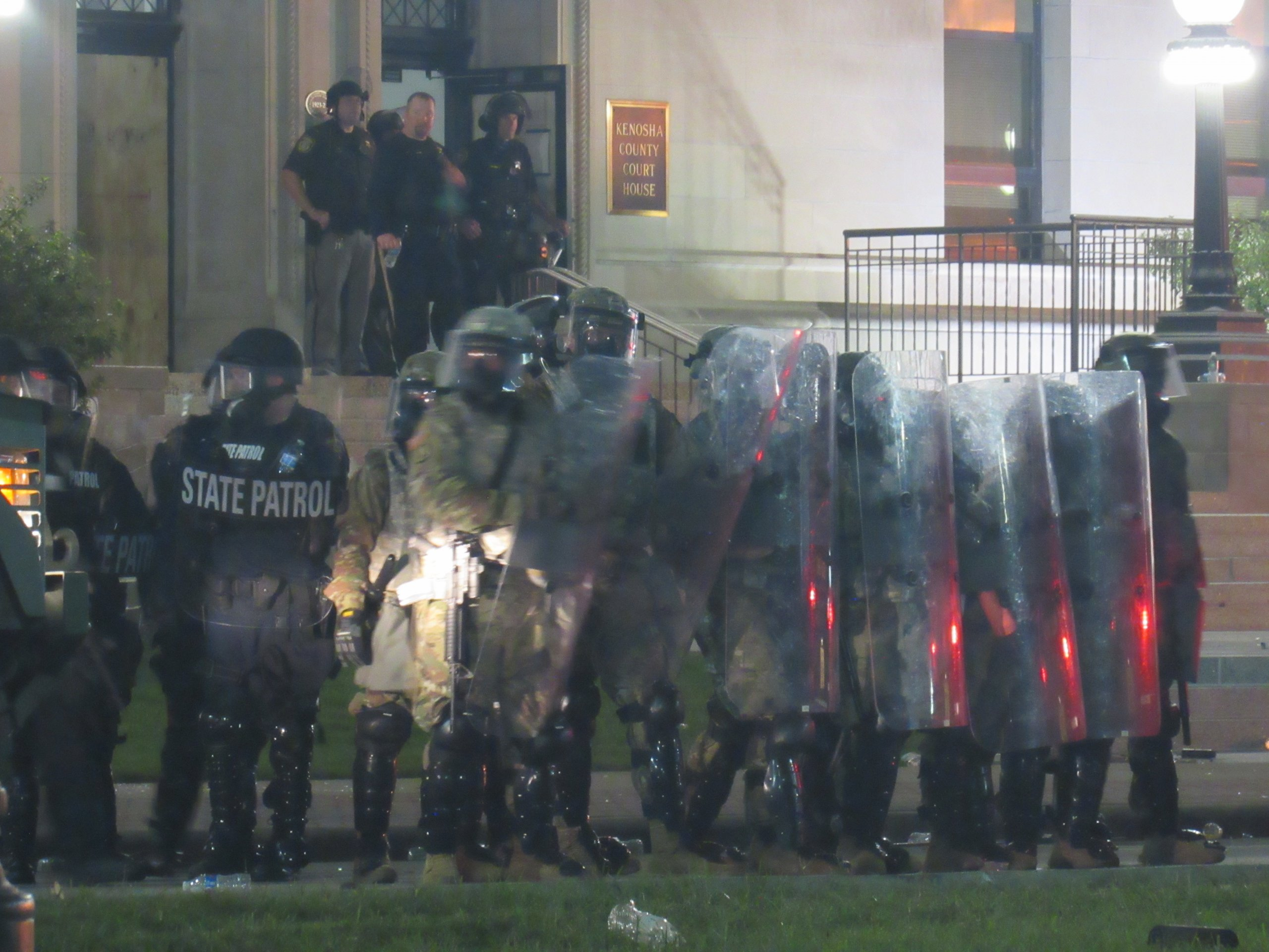 Kenosha law enforcement form up with riot shields, long rifles, and armored vehicles. (Photo by Isiah Holmes)