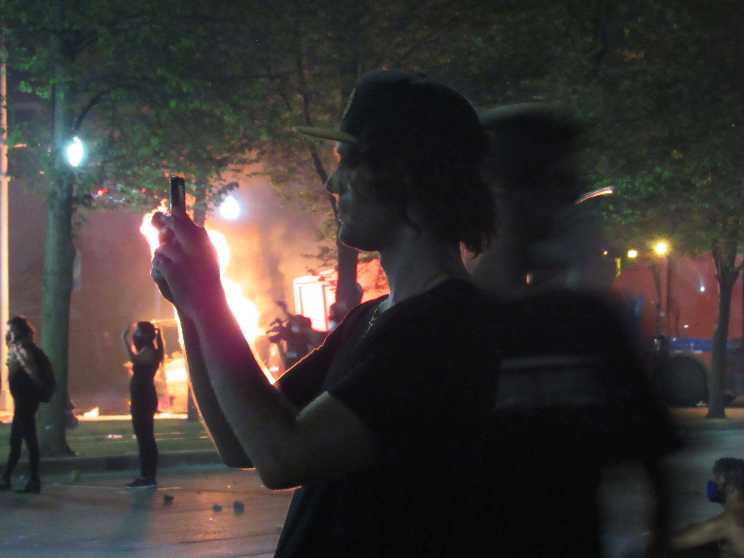 People look on at the clash between police and protesters in Kenosha on August 24, 2020. (Photo by Isiah Holmes)