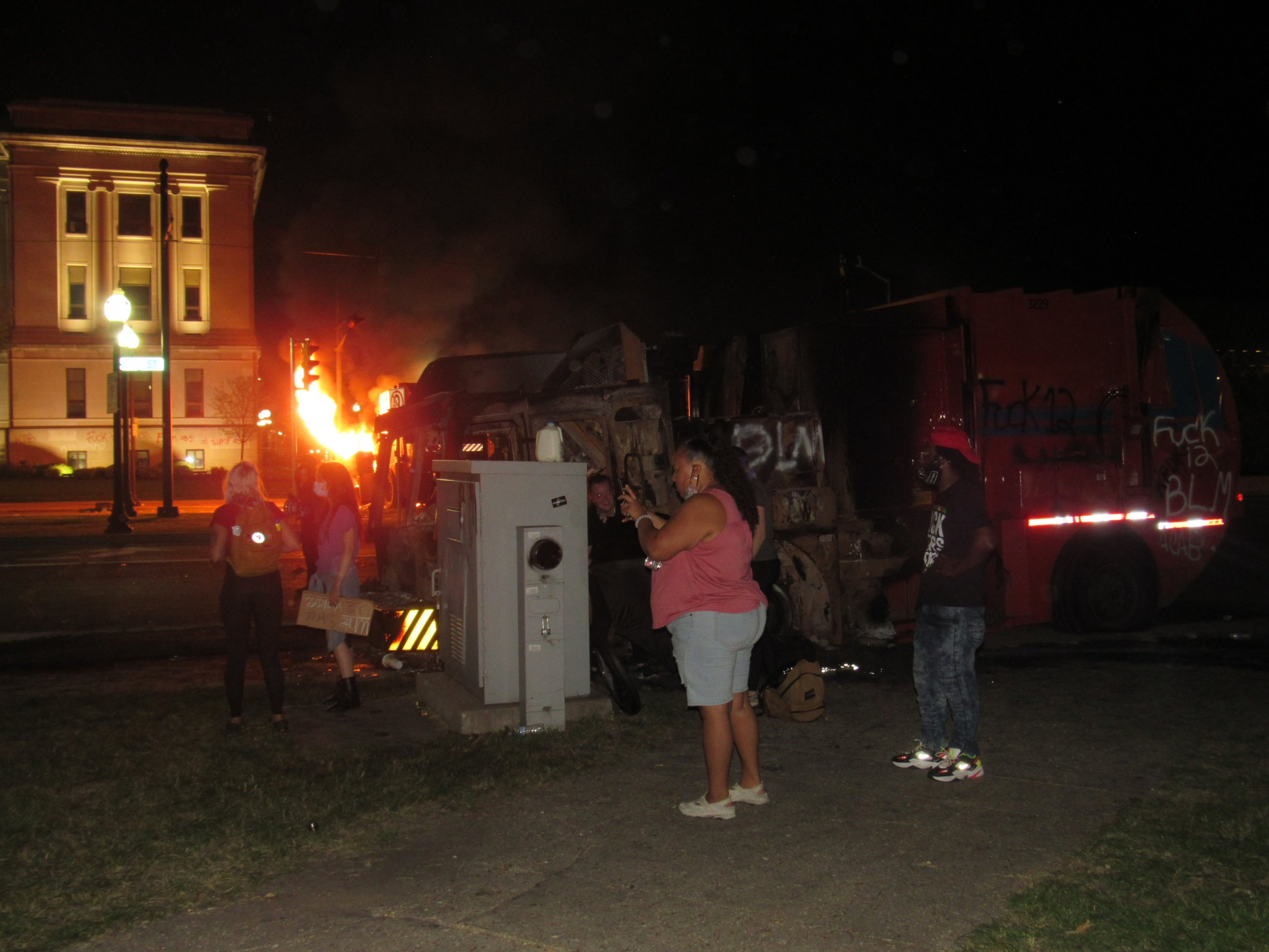 People look on as protesters clash with police, and vehicles burned around them. (Photo by Isiah Holmes)