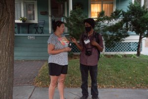 Wisconsin Examiner journalist Isiah Holmes talks with Lisa Cole as the march goes by. (Photo courtesy of Ryan Berg)