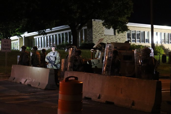 What appear to be National Guard soldiers stand outside Wauwatosa City Hall on Oct. 7, watching protests march past a line of militarized police officers. (Photo by Isiah Holmes)