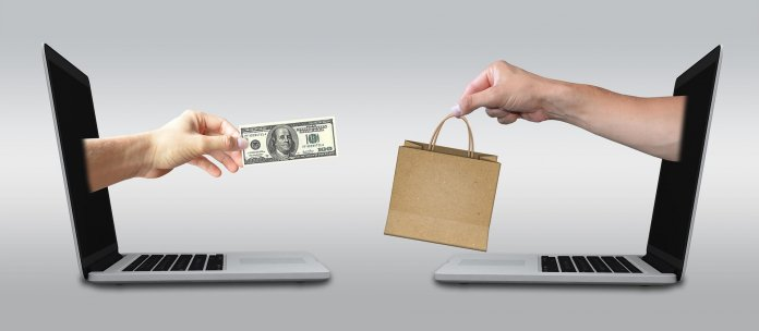e-commerce: hands reaching out of laptops to exchange money for shopping bag.