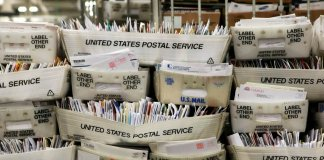 Stacks of boxes holding mail are seen at a U.S. Post Office sorting center. Photo by Justin Sullivan | Getty Images