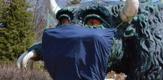 The giant hodag statue wearing a COVID-19 mask