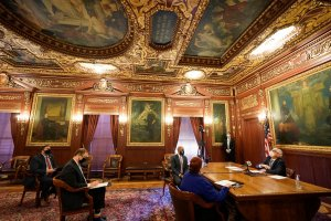 "Gov. Tony Evers reads the words ""The will of the people is the law of the land,"" on the ceiling of governor's conference room in the Capitol as Wisconsin's 10 electors meet on Dec. 14 to deliver the state's votes for Joe Biden in the 2020 presidential election. (Photo by Morry Gash, Associated Press)"