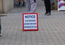 Sign on pavement: Notice no electioneering beyond this point