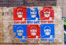 street art reading Stay Safe defaced by crossing out and words Masks off