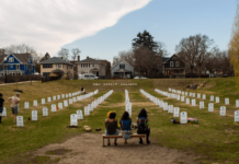 People sit at the Say Their Names Cemetery during the People's Power Love Fest at George Floyd Square Sunday, April 4, 2021. Photo by Nicole Neri/Minnesota Reformer.
