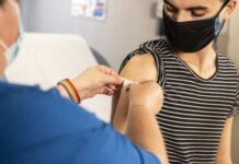 Double masked teen getting vaccine